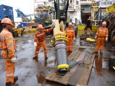 Workers handling a mooring connector in the Usan field